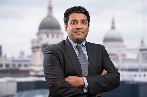 LinkedIn headshot with London businessman and City background.