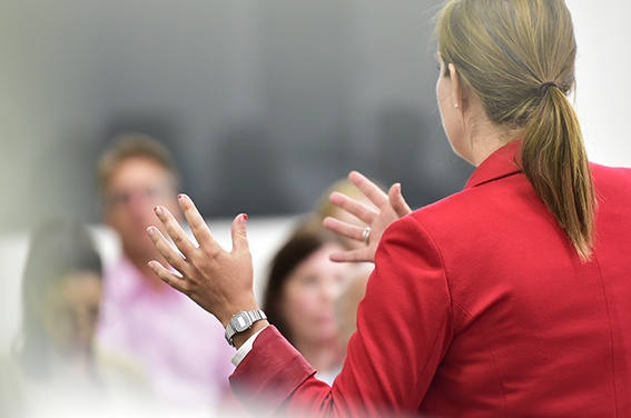 Reportage corporate photograph of businesswoman presenting to clients in London boardroom