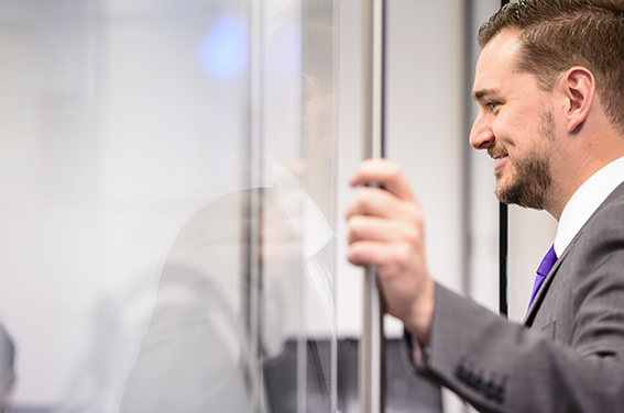 Smiling managing director talking to staff in his London office. Reportage corporate photographer