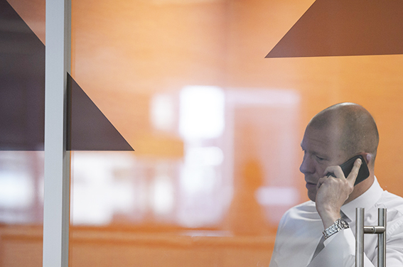 Generic corporate imagery in London offices of man using mobile phone