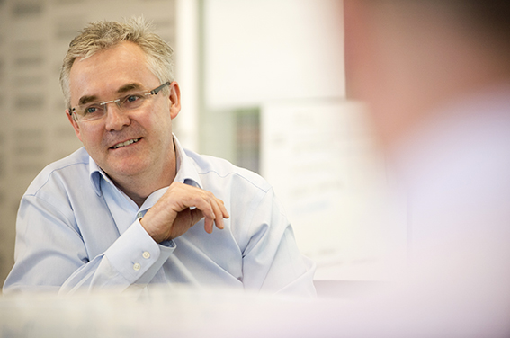 Corporate informal and in action photograph of businessman in meeting. Corporate photography London