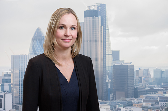 Corporate headshot of businesswoman with Cityscape of London's financial district behind her.