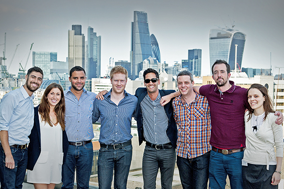 Team photograph on London roof with The City in the background.